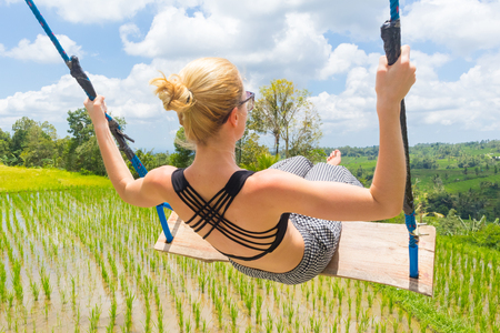 Happy sporty female traveller swinging on wooden swing, enjoying summer vacation in pristine green nature at Jatiluwih rice terraces on Bali, Indonesia. Freedom and life enjoying concept. Stockfoto