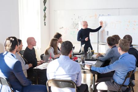 Reunión informal relajada de la empresa de inicio de negocios de TI. Líder del equipo discutiendo y haciendo una lluvia de ideas sobre nuevos enfoques e ideas con sus colegas. Concepto de emprendimiento y negocios de puesta en marcha.