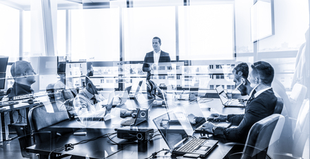 Successful team leader and business owner leading informal in-house business meeting. Businessman working on laptop in foreground. Business and entrepreneurship concept. Blue toned grayscale. Stockfoto