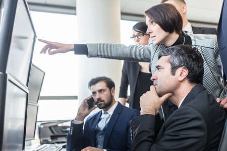 Business people looking at data on multiple computer screens in corporate office. Businesswoman pointing on screen. Business team trading online. Business, entrepreneurship and team work concept.