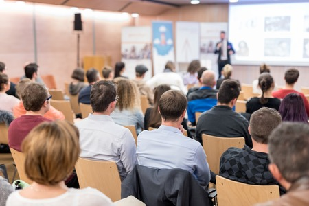 Speaker giving a talk in conference hall at business event. Audience at the conference hall. Business and Entrepreneurship concept. Focus on unrecognizable people in audience. Standard-Bild - 122325637