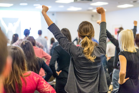 Symposium für Lebensberatung. Sprecher, der eine interaktive Motivationsrede beim Business-Workshop hält. Rückansicht von unerkennbaren Teilnehmern, die sich gestärkt und motiviert fühlen, die Hände hoch in die Luft gehoben.