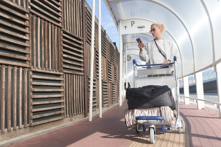 Young casual woman using mobile phone application while transporting luggage from arrival parking to international airport departure termainal by luggage trolley.