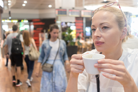 Portrait of a casual young blond woman having a cup of coffee, sitting and waiting in cafe indoors of an airport, station, food court or shopping mall.