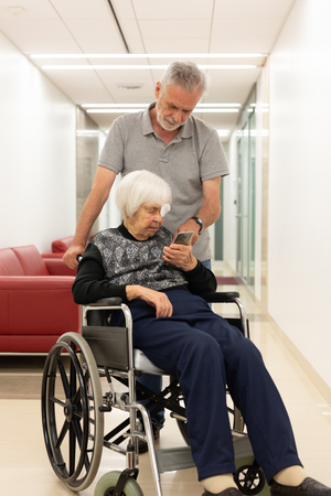 Middle aged man showing and helping elderly 95 years old woman sitting at the wheelchair how to use modern mobile phone application to monitor her therapy and entertain herself.