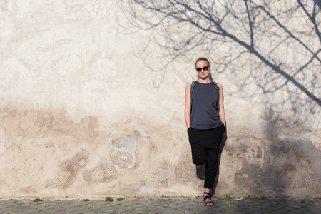 Modern trendy fashionable woman wearing sunglasses leaning against old textured retro wall with tree shadow falling on the wall. Graphical and textured artisic image. Stok Fotoğraf