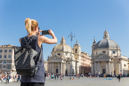 Female tourist with a fashinable vintage hipster backpack taking photo of Piazza del Popolo, Peoples Square, in Rome, Italy by her mobile phone. Stok Fotoğraf