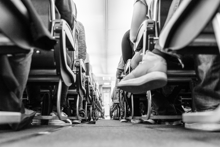 Low agle view of passenegers commercial airplane aisle with passenegers sitting on their seats while flying. Black and white image. Stok Fotoğraf