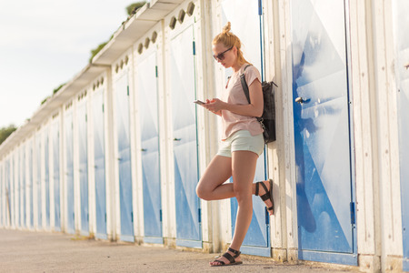 Blonde young female traveler wearing summer style clothing, using mobile phone, leaning against retro blue beach dressing rooms at summer time vacation in Sistiana, Italy.
