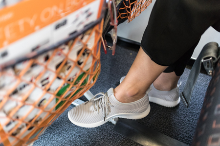 Female passenger with lack of leg space on long commercial airplane flight. Focus on casual sporty sneakers.