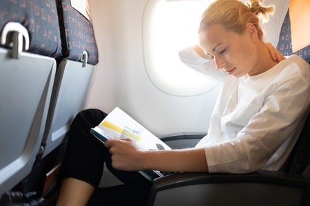 Woman feeling neck pain while reading in flight magazine on long intercontinental airplane flight. Female traveler uncomfortable seated in passenger cabin. Sun shining trough airplane window. Stok Fotoğraf