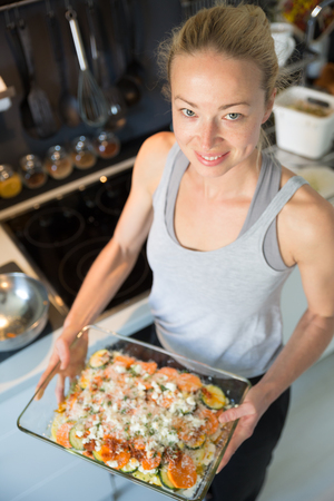 Smiling young healthy woman holding and proudly showing glass baking try with row vegetarian dish ingredients before placing it into oven. Healthy home-cooked everyday vegetarian food.