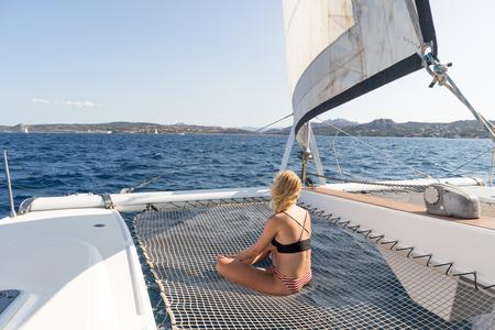 Bella donna che si rilassa durante una crociera in barca a vela estiva, seduta e prendendo il sole sull'amaca del lussuoso catamarano che naviga intorno all'arcipelago della Maddalena, in Sardegna, nella calda luce del pomeriggio.