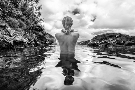 Rear view of beautiful naked woman bathing and relaxing in natural swimming pool before the 500 feet waterfall in natural park on tropical island of Mauritius. Black and white image Stok Fotoğraf