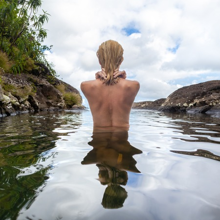 Rear view of beautiful naked woman bathing and relaxing in natural swimming pool before the 500 feet waterfall in natural park on tropical island of Mauritius. 写真素材