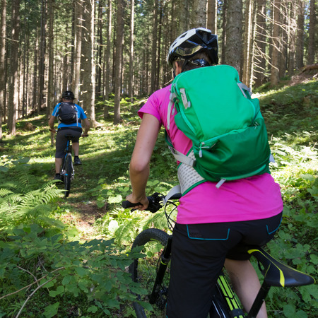 Active sporty couple riding mountain bikes on demanding forest trail.