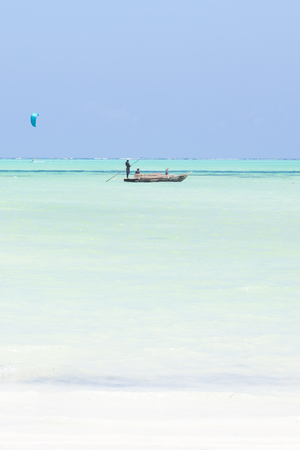 Solitary fishing boat and a kite surfer on picture perfect white sandy beach with turquoise blue sea, Paje, Zanzibar, Tanzania. Copy space. Stok Fotoğraf