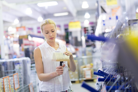 Female customer buying painting roller in household retail store.