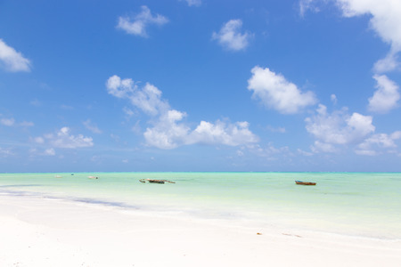 Traditional wooden fishing boats on picture perfect white sandy beach with turquoise blue sea, Paje, Zanzibar, Tanzania. Copy space. Stok Fotoğraf
