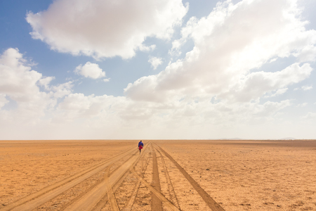 Solitary masai worrior walking along salt lake desert road in Kenya, Amboseli Natural Park, Africa.