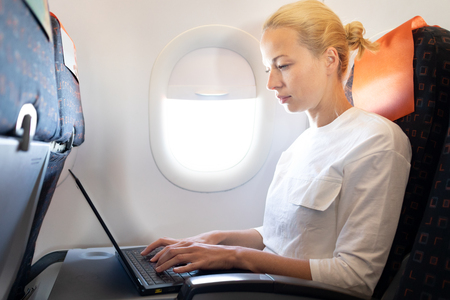 Attractive caucasian female passenger working at modern laptop computer using wireless connection on board of commercial airplane flight. Stok Fotoğraf