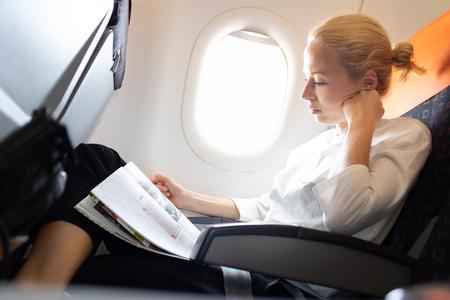 Woman reading in flight magazine on airplane. Female traveler reading seated in passanger cabin. Sun shining trough airplane window.