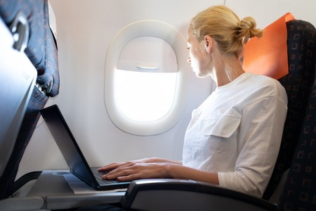 Attractive caucasian female passenger looking through the plain window while working on modern laptop computer using wireless connection on board of commercial airplane flight.