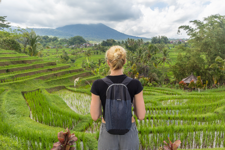 Casual caucasian female tourist wearing small backpack looking at beautiful green rice fields and terraces of Jatiluwih on Bali island, Indonesia.