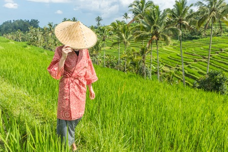 Relaxed fashionable caucasian woman wearing red asian style kimono and traditional asian paddy hat walking amoung beautiful green rice fields and terraces on Bali island.