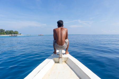 Unrecognizable Local Sporty Guy Sitting Topless at the Bow of Traditional White Wooden Sail Boat, Enjoying the Breeze, Looking At Beautiful Blue Sea of Gili Islands near Bali, Indonesia.
