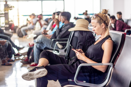 Casual sporty young blond female traveler talking on her cell phone while waiting to board a plane at the departure gates at the asian airport terminal.