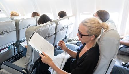 Female traveler reading magazine on airplane during flight. Female traveler reading seated in passanger cabin.