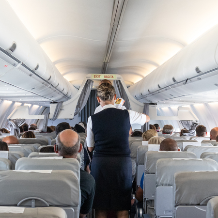 Interior of commercial airplane with flight attandant serving passengers on seats during flight. Stewardess in dark blue uniform walking the aisle. Stok Fotoğraf