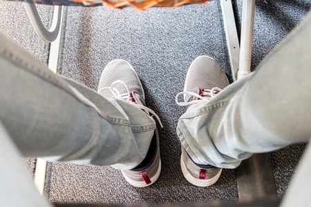 Male passenger with lack of leg space on long commercial airplane flight. Focus on casual sporty sneakers.