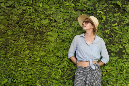 Portrait of a beautiful female traveler. Smiling young woman in summer hat wearing sunglasses, standing in front of lush tropical plant greenery wall background. Copy space on the green wall.