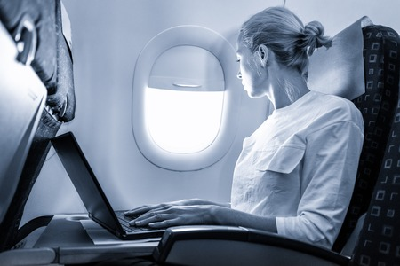 Attractive caucasian female passenger looking through the plain window while working on modern laptop computer using wireless connection on board of commercial flight. Blue toned greyscale image.
