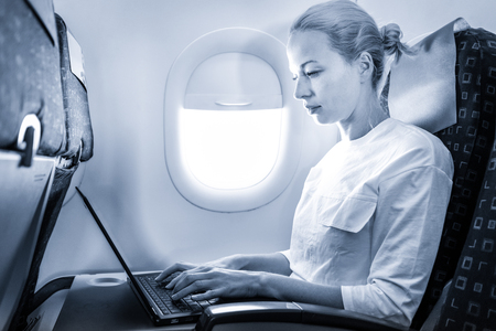 Attractive caucasian female passenger working at modern laptop computer using wireless connection on board of commercial airplane flight. Blue toned greyscale image. Stok Fotoğraf