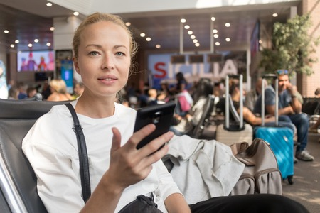 Casual blond young woman reading on her mobile phone while waiting to board a plane at the departure gates at the airport terminal. Travel concept.