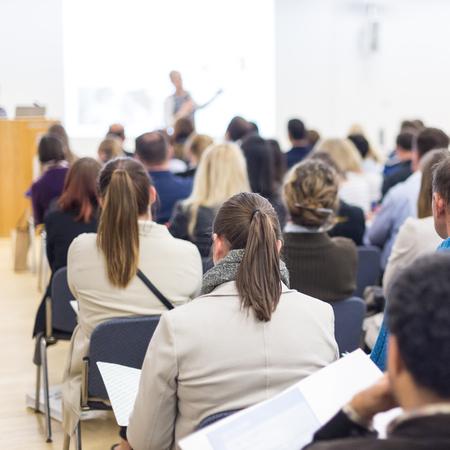 Symposium für Wirtschaft und Unternehmertum. Sprecherin, die ein Gespräch beim Geschäftstreffen gibt. Publikum im Konferenzsaal. Rückansicht eines unbekannten Teilnehmers am Publikum. Kopieren Sie Platz auf dem weißen Bildschirm.