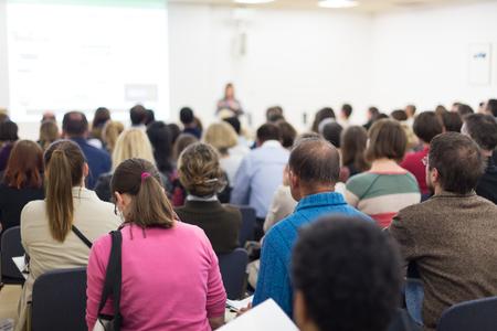 Zakelijk en ondernemerschap symposium. Vrouwelijke spreker die een bespreking geeft op commerciële vergadering. Publiek in conferentiezaal. Achteraanzicht van niet-herkende deelnemers die aantekeningen maken in het publiek. Stockfoto