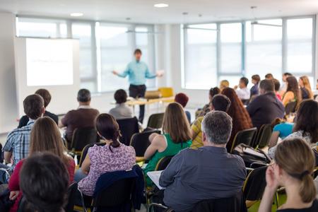 Simposio de negocios y emprendimiento. Ponente dando una charla en una reunión de negocios. Audiencia en la sala de conferencias. Vista posterior del participante no reconocido en la audiencia. Foto de archivo