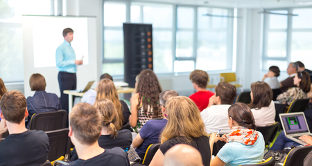 Simposio de negocios y emprendimiento. Ponente dando una charla en una reunión de negocios. Audiencia en la sala de conferencias. Vista posterior del participante no reconocido en la audiencia.