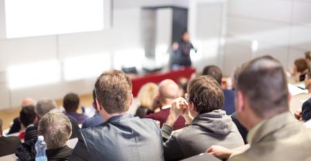 Sprecher hält einen Vortrag im Konferenzsaal bei einer Geschäftsveranstaltung. Publikum im Konferenzsaal. Business- und Entrepreneurship-Konzept. Konzentrieren Sie sich auf nicht erkennbare Personen im Publikum.