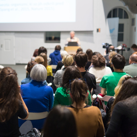 Männlicher Sprecher, der Präsentation im Hörsaal an der Universitätswerkstatt gibt. Publikum im Konferenzsaal. Rückansicht eines nicht erkannten Teilnehmers im Publikum. Wissenschaftliche Konferenzveranstaltung.