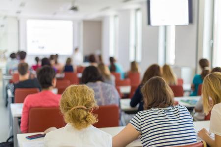 Conférencier donnant une présentation dans une salle de conférence à l'université. Les participants écoutent la conférence et prennent des notes. Banque d'images