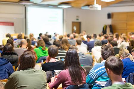 Rondetafelgesprek bij workshop ondernemerschap en ondernemerschap. Publiek in de conferentiezaal. Presentatie in collegezaal op de universiteit. Deelnemers luisteren naar de lezing en maken aantekeningen.