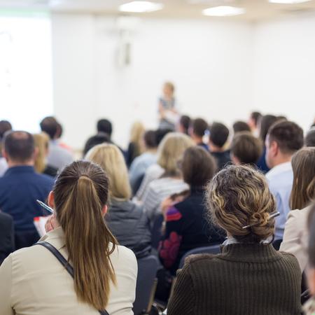 Simposio su imprese e imprenditoria. Oratore femminile che tiene un discorso alla riunione d'affari. Pubblico nella sala conferenze. Retrovisione del partecipante non riconosciuto nel pubblico. Copia spazio su schermo bianco.