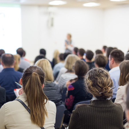 Zakelijk en ondernemerschap symposium. Vrouwelijke spreker die een bespreking geeft op commerciële vergadering. Publiek in conferentiezaal. Achteraanzicht van niet-herkende deelnemer in publiek. Kopieer de ruimte op het witte scherm.