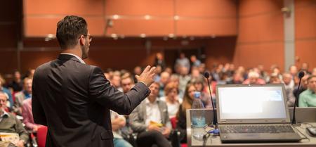 Prelegent wygłaszający prelekcję na korporacyjnej konferencji biznesowej. Publiczność w sali konferencyjnej. Wydarzenie Biznes i Przedsiębiorczość.