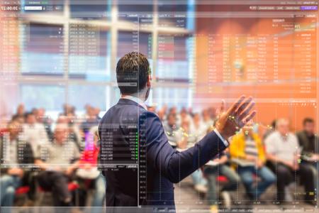 Speaker at business conference with public presentations. Audience at the conference hall. Trough the transparent presentation screen view. Charts and tables can be seen in forground. Stock Photo